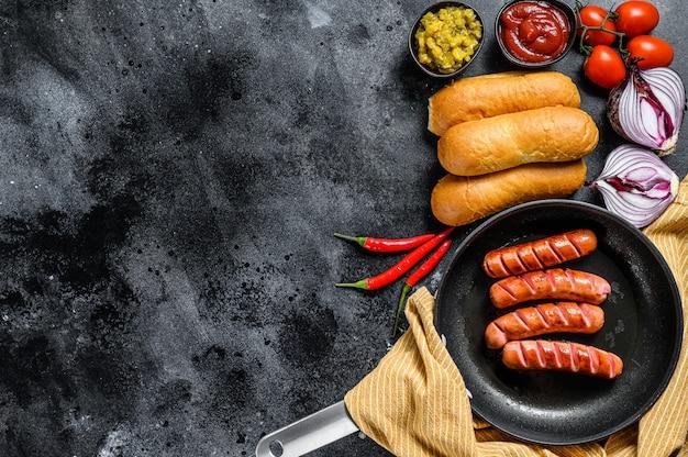 Zutaten für hot dogs auf einem schwarzen tisch