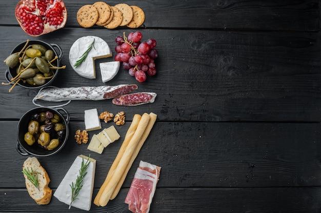 Zutaten für italienisches essen, fleischkäse, kräuter, auf schwarzem holztisch, flach gelegt