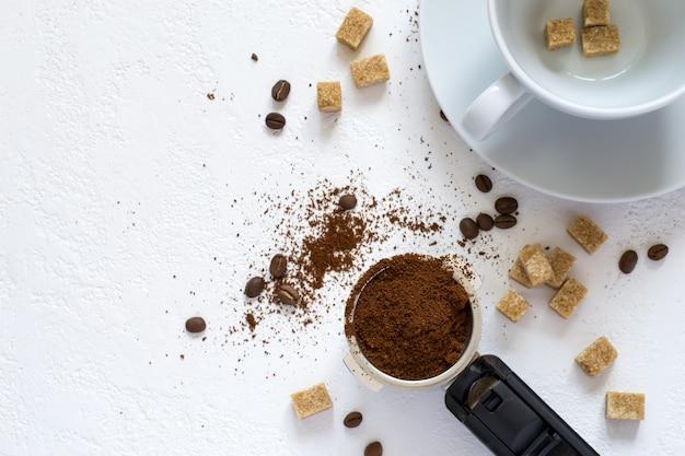 Zutaten für kaffee: gemahlener kaffee im horn der kaffeemaschine, zucker und eine tasse. draufsicht mit kopienraum