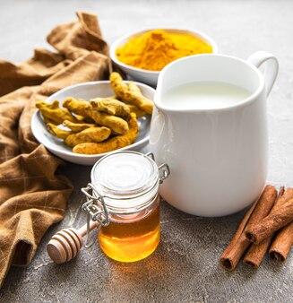 Zutaten für kurkuma latte. gemahlene kurkuma, curcuma-wurzel, zimt, milchkrug über grauem betonhintergrund. draufsicht, kopierraum