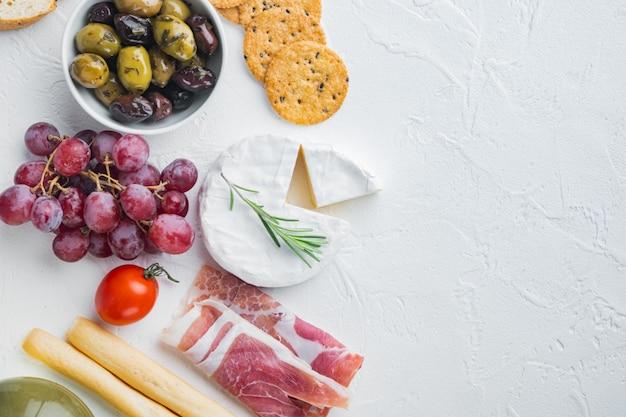 Zutaten für mediterranes essen, fleischkäse, kräuter auf weißem tisch, flach liegen