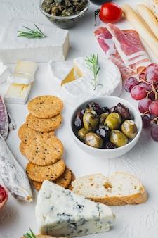 Zutaten für mediterranes essen, fleischkäse, kräuter auf weißem tisch