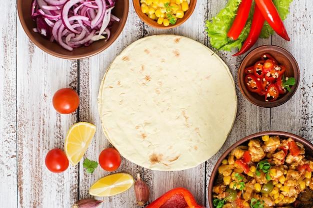 Zutaten für mexikanische tacos mit fleisch, mais und oliven auf hölzernen hintergrund. ansicht von oben