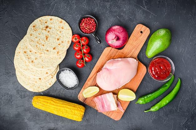 Zutaten für mexikanische tacos mit hühnerfleisch, maistortilla, salsa, chili über schwarzem hintergrund, draufsicht.