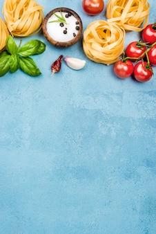 Zutaten für nudeln mit gemüse auf dem schreibtisch