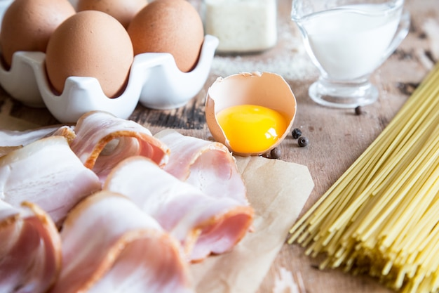 Zutaten für pasta carbonara mit speck, käse, sahne und eigelb auf holztisch