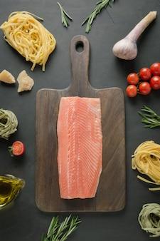 Zutaten für pasta tagliatelle mit forelle auf schneidebrett. von oben betrachten.