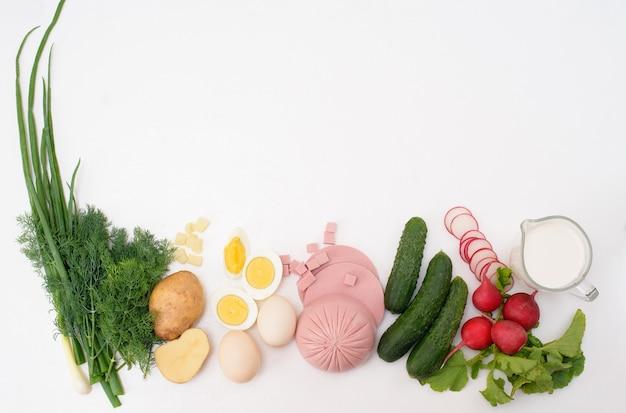 Zutaten für russische nationale kalte okroschka-suppe auf hellem hintergrund. kartoffeln, radieschen, wurst, zwiebeln, kräuter, eier. der blick von oben