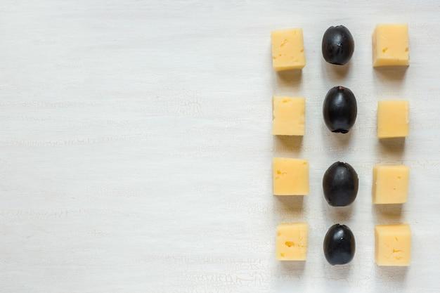 Zutaten für snacks, käse mit oliven auf einem weißen tisch