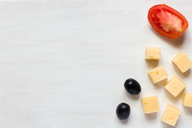 Zutaten für snacks, käse mit oliven und tomaten auf einem weißen tisch