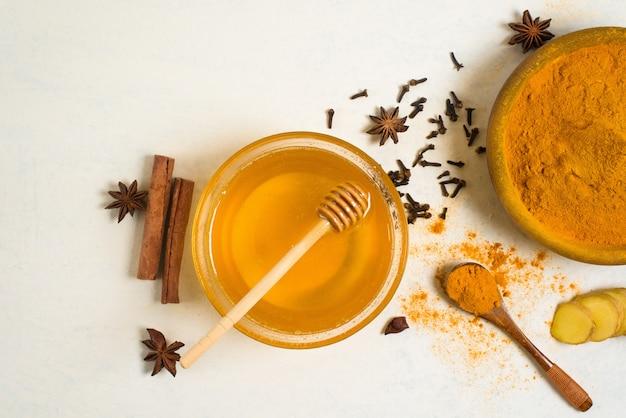 Zutaten für traditionelle indische goldmilch mit kurkuma, ingwer, gewürzen, honig.