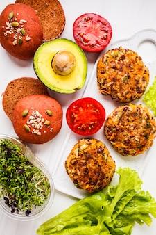 Zutaten für vegane burger auf einem weißen bohnenburger, rosa rote-bete-brötchen, sprossen, avocado und gemüse,