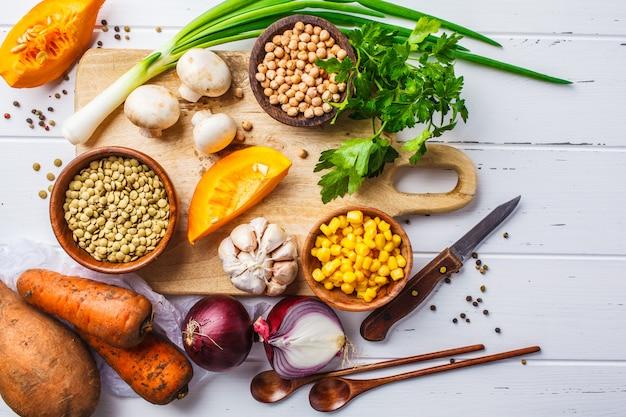 Zutaten für vegane gemüsesuppe mit linsen, pilzen und kichererbsen auf weißem hintergrund.