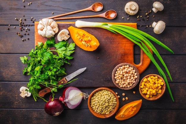 Zutaten für vegane gemüsesuppe mit linsen und kichererbsen auf dunklem holz