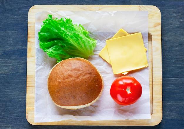 Zutaten für vegetarisches cheeseburgerbrötchen, zwiebeln, salat, tom