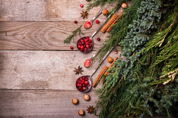 Zutaten für weihnachten, winterplätzchen backen. lebkuchen, obstkuchen, saisonale getränke. moosbeeren, getrocknete orangen, zimt, gewürze auf einem holztisch, draufsicht des kopienraumes.