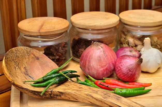 Zutaten kochen. gewürz und kräuter mit zwiebel und knoblauch auf holzbrett