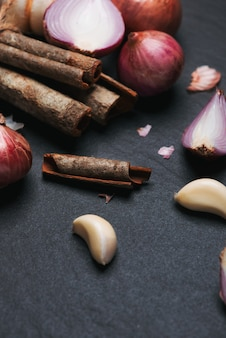 Zutaten kochen: zimtstangen und knoblauch auf schwarzem steintisch.