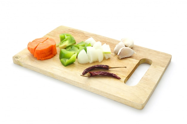 Zutaten-set aus karotte, paprika, paprika, paprika, zwiebel, knoblauch, trockenem chili auf dem hackklotz