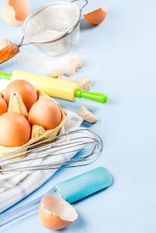 Zutaten und utensilien zum kochen von ei, mehl, zucker, schneebesen, nudelholz