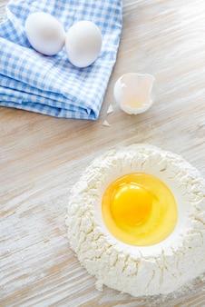 Zutaten und werkzeuge zum backen - mehl, eier und glas milch auf dem rustikalen holztisch. hausgemachte pastazubereitung