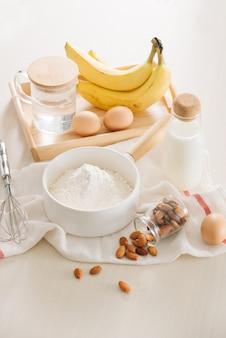 Zutaten und werkzeuge zur herstellung von bananenkuchen auf weißer oberfläche