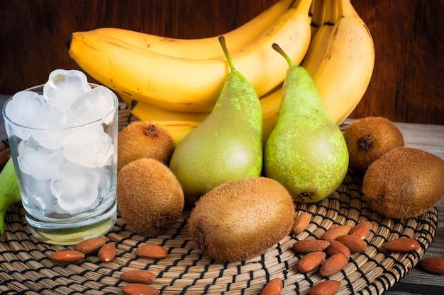 Zutaten von grünen smoothies mit bananen, kiwi, birnen und eis