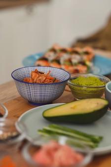 Zutaten von japanischem sushi und brötchen stillleben reis frisches avocado-lachsfilet und wassabi