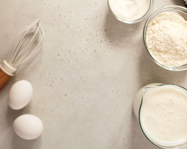 Zutaten zum backen mit mehl und einem kulinarischen schneebesen mit platz für text, rezept