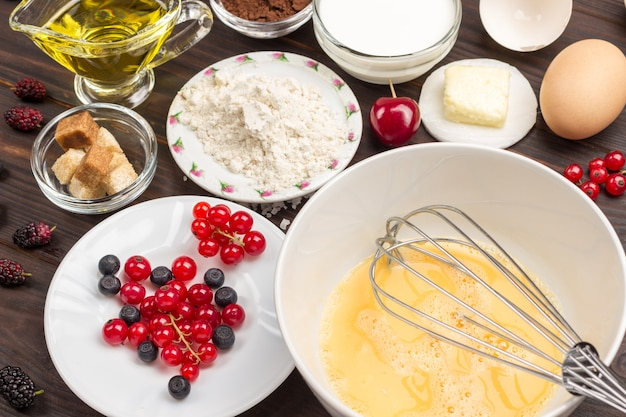 Zutaten zum backen von beerenkuchen. metall schneebesen in schüssel mit zerbrochenem ei