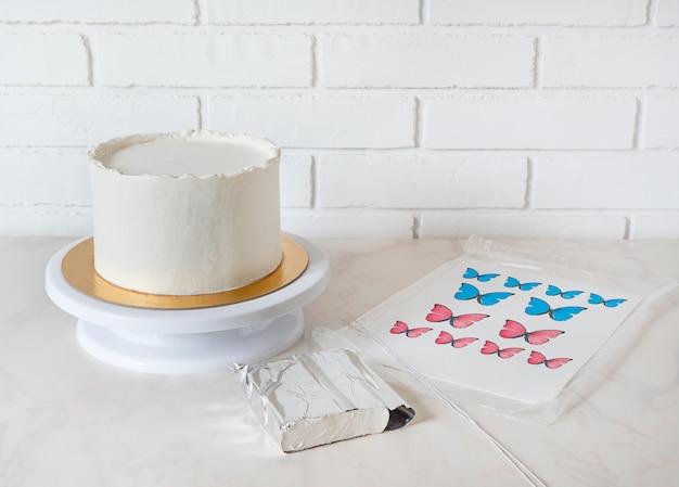 Zutaten zum dekorieren von weißem kuchen mit roten und blauen schmetterlingen