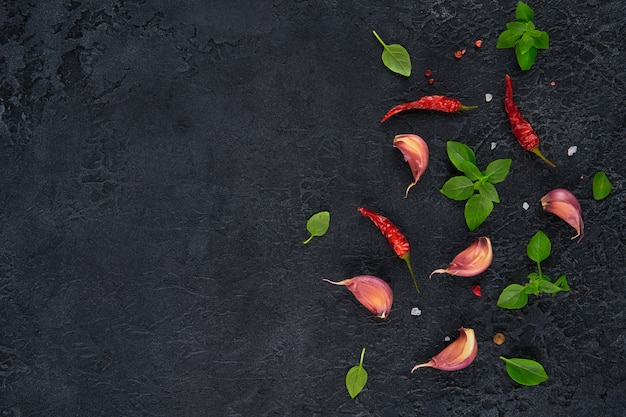 Zutaten zum kochen. draufsicht von knoblauch, basilikum und chili auf dunklem tisch.