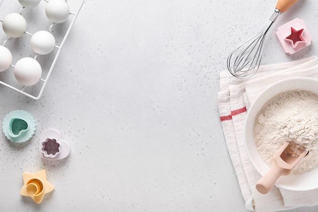 Zutaten zum kochen hausgemachtes backen. backen hintergrund mit mehl, eiern, küchengeräten, utensilien und keksformen auf weißem marmortisch. ansicht von oben. flacher lay-stil. attrappe, lehrmodell, simulation.