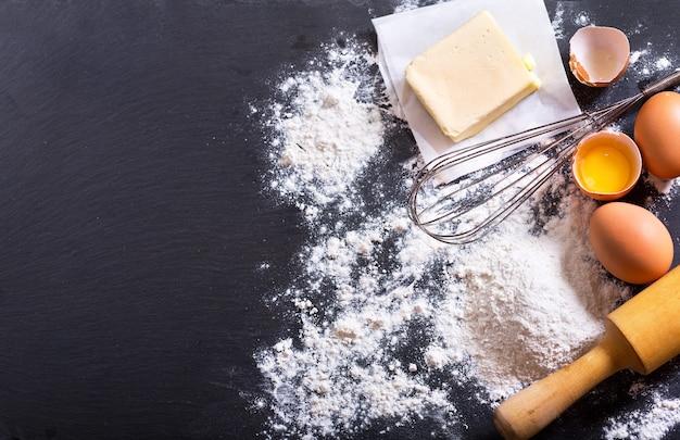 Zutaten zum kochen: mehl, butter, eier im dunkeln