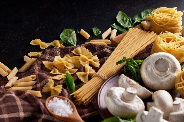 Zutaten zum kochen traditioneller nudeln mit pilzen auf dunkler steinoberfläche