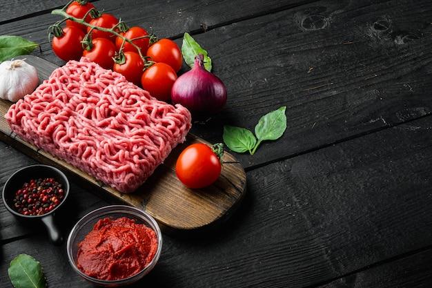 Zutaten zum kochen von bolognese-sauce, hackfleisch-tomaten und kräutern auf holzschneidebrett