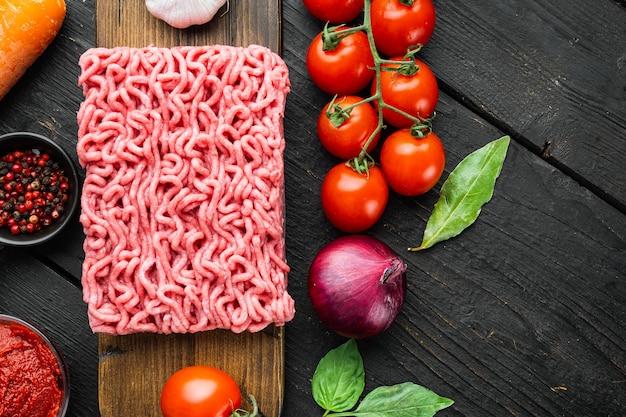 Zutaten zum kochen von bolognese-sauce, rinderhackfleisch-tomaten und kräutern