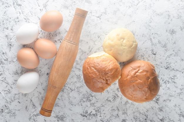 Zutaten zum kochen von brötchen zu hause. eier, nudelholz, brötchen auf einem weißen betontisch