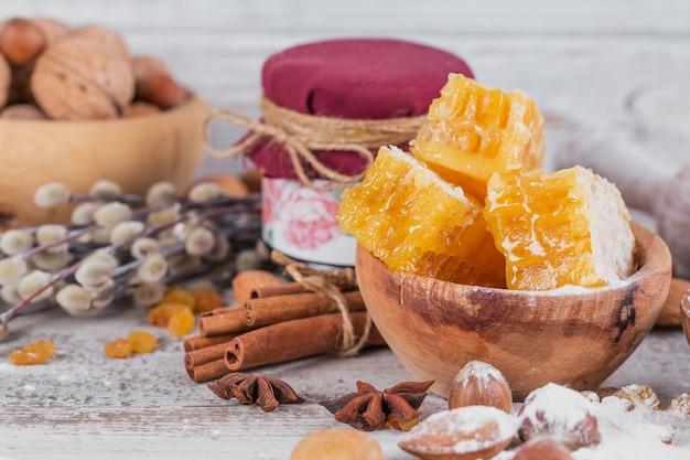 Zutaten zum kochen von brot oder keksen mit bienenwabe, mehl, rosinen, nussmischung, gewürzen
