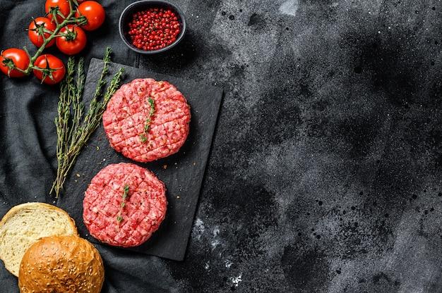 Zutaten zum kochen von burgern. hackfleischpastetchen, brötchen, tomaten, kräuter und gewürze