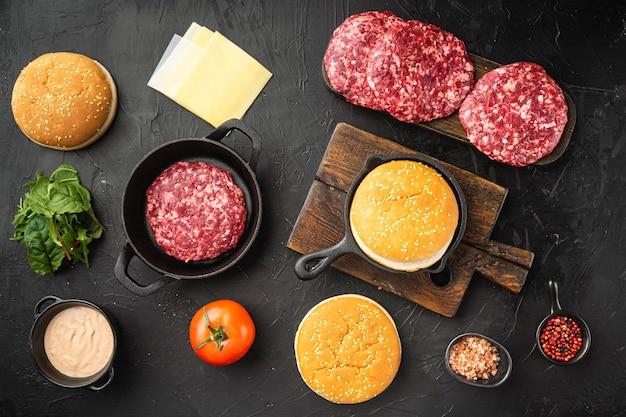 Zutaten zum kochen von burgern. rohe rinderhackfleischkoteletts, auf schwarzem steinhintergrund, draufsicht flach