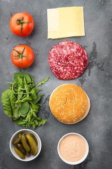 Zutaten zum kochen von burgern. rohes rinderhackschnitzel-set, auf grauem stein