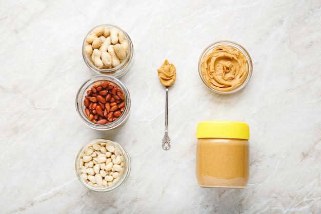 Zutaten zum kochen von erdnussbutter. geschälte und ungeschälte erdnüsse, erdnussbutter im glas und erdnussbutter in einem löffel auf weißem marmorhintergrund. flache lage des kochens des natürlichen gesunden nahrungsmittelkonzepts