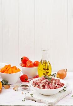Zutaten zum kochen von hähnchenherzen mit kürbis und tomaten in tomatensauce. die beilage wird mit gekochtem reis serviert.