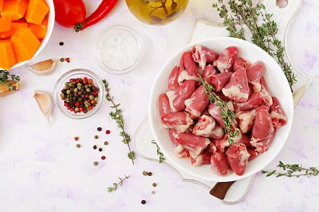 Zutaten zum kochen von hühnerherzen mit kürbis und tomaten in tomatensauce. die beilage wird mit gekochtem reis serviert. flach liegen. draufsicht.