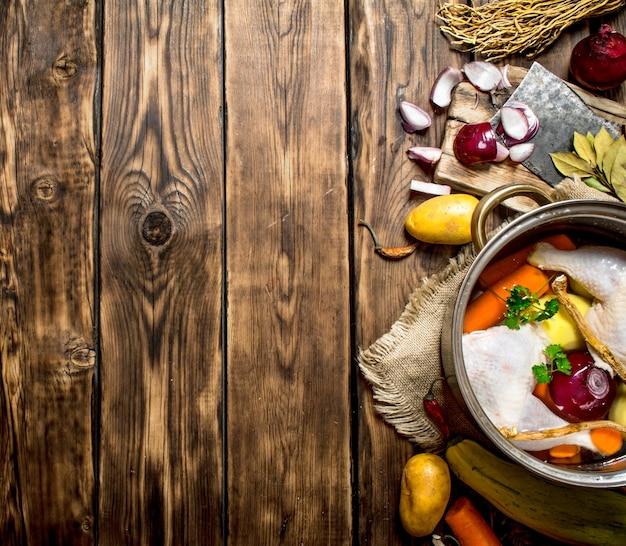 Zutaten zum kochen von hühnersuppe mit gemüse und gewürzen. auf einem holztisch.