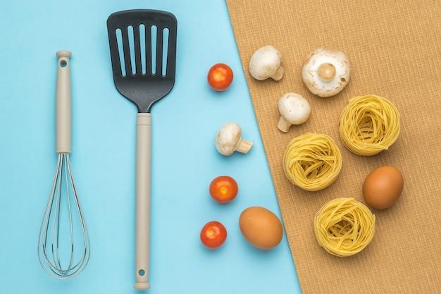 Zutaten zum kochen von nudeln mit pilzen und tomaten und küchenutensilien.