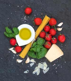 Zutaten zum kochen von nudeln. spaghetti, olivenöl, knoblauch, parmesan, tomaten und frischem basilikum