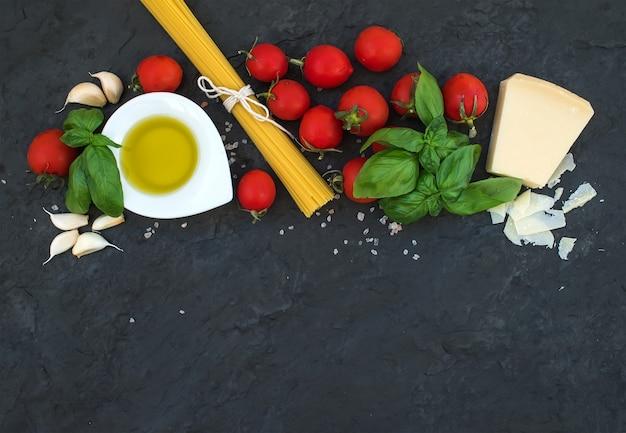 Zutaten zum kochen von nudeln. spaghetti, olivenöl, knoblauch, parmesan, tomaten und frisches basilikum auf schwarzem schiefer