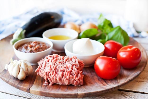 Zutaten zum kochen von parmigiana di melanzane: gebackene auberginen - italien, sizilien. auf dem holztisch.